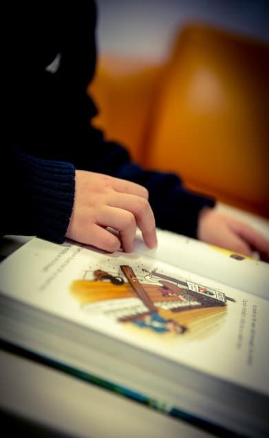 boy reading book with compass